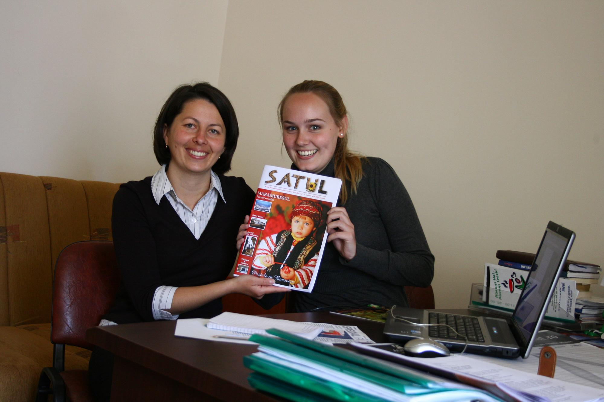An intern holds up a magazine at a journalism placement in Romania